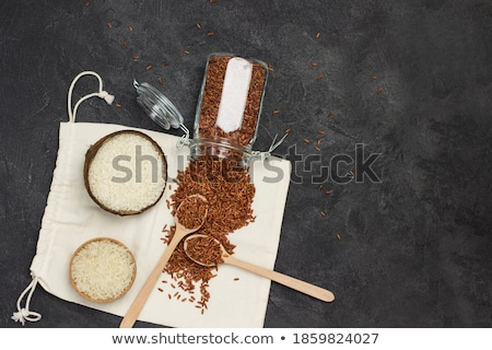 Wooden spoon and linen bag of raw organic red rice on white background. Healthy food.  Stock photo © DenisMArt