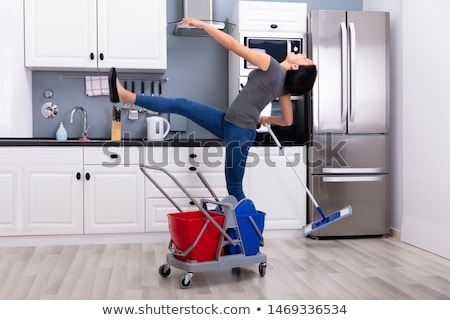 Stok fotoğraf: Woman Slipping While Mopping Floor In Kitchen