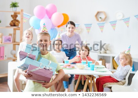 Cheerful little boy with stack of giftboxes standing in front of camera Stock photo © pressmaster