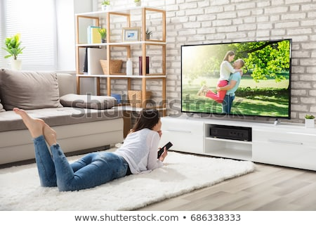Woman Relaxing on Sofa by Watching TV Programs Stock photo © robuart