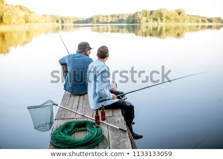 Człowiek rybak posiedzenia molo wędka koszyka Zdjęcia stock © robuart