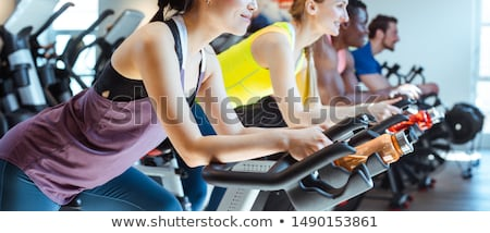 Stok fotoğraf: Caucasian Man And Her Friends On Fitness Bike In Gym