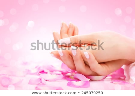 Manicure, Hands spa Beautiful woman hands, soft skin, beautiful nails with pink rose flowers petals. Stock photo © serdechny