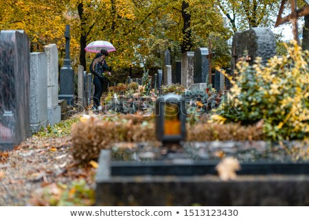 Stockfoto: Graves On Cemetery In Autumn With A Couple Mourning The Dead