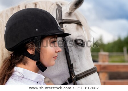 Profile of young active woman in equestrian helmet and white purebred horse Stock photo © pressmaster