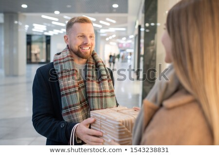 Cheerful young man congratulating his wife on Christmas and passing her giftbox Stock photo © pressmaster