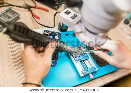 Tweezers in hands of repairman using microscope during work with tiny details Stock photo © pressmaster