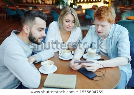 Grupo faculdade amigos café assistindo curioso Foto stock © pressmaster