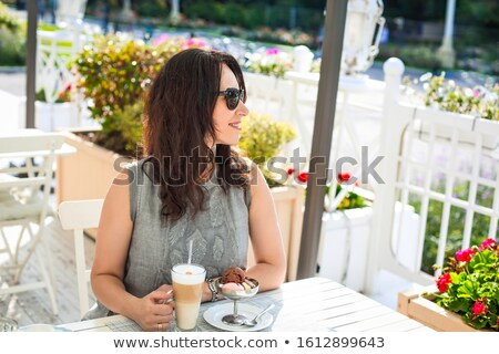 Woman drinking latte coffee and eating ice cream in outdoor cafe Stock photo © dashapetrenko