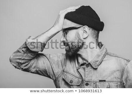 Sideways portrait of bearded male has regretful expression, keep Stock photo © vkstudio