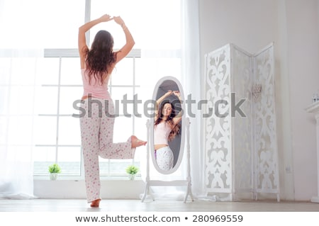 happy young woman in pajama stretching Stock photo © dolgachov