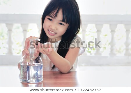 Cute girl using hand gel to clean hands Stock photo © bluering