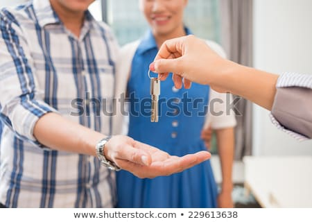 Stock photo: Estate-agent handing keys to new home owners