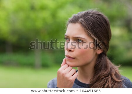 Young thoughtful girl standing upright in the countryside with her hand on chin Stock photo © wavebreak_media
