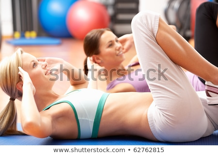 Portrait of happy woman doing sit-ups on exercise mat stock photo © wavebreak_media