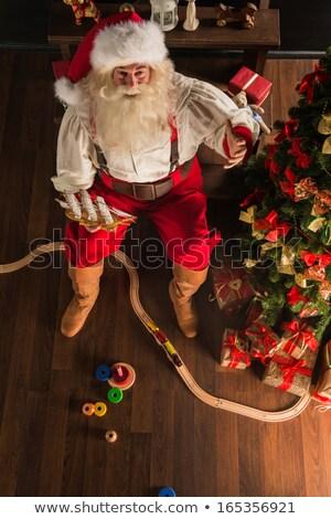 Santa Claus at home playing with new toys at dark room Stock photo © HASLOO