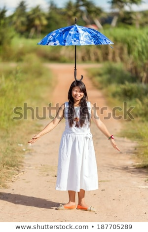 Young Thai girl balancing an umbrella on her head Stock photo © smithore