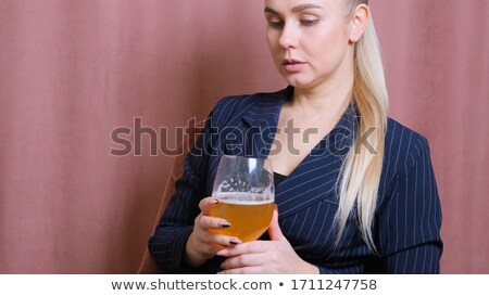 serious blond woman holding a glass at the kitchen stock photo © juniart