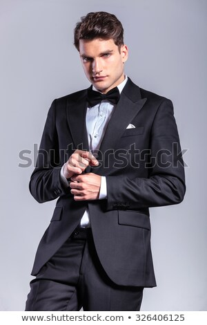 business man smiling at the camera while fixing his tie. Stock photo © feedough