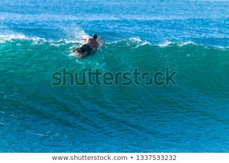 surfer paddles out to the waves stock photo © klinker