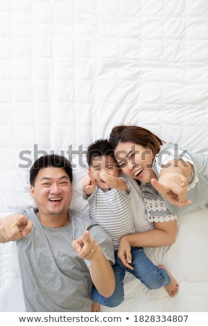 man lying in bed pointing and smiling stock photo © monkey_business