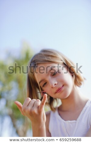 Girl inspecting dragonfly on her finger Stock photo © IS2