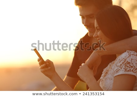 couple of man and woman sitting back to back and reading phone stock photo © studiostoks
