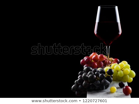 Elegant glass of red wine with dark and red and green grapes on wooden board on black background.  Stock photo © DenisMArt