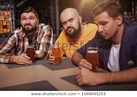 friends clinking beer and watching soccer game Stock photo © dolgachov