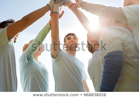 group of volunteers making high five outdoors stock photo © dolgachov