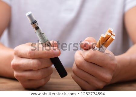 Man Holding Vape And Tobacco Cigarettes Stock photo © AndreyPopov