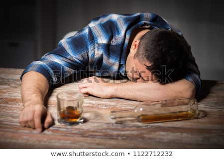 Stock photo: drunk man with glass of alcohol on table at night