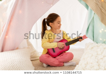 girl playing toy guitar in kids tent at home Stock photo © dolgachov