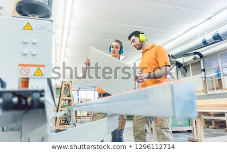 Carpenter in furniture factory inspecting piece in QA Stock photo © Kzenon