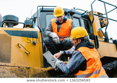 worker with heavy excavation machinery in mining operation stock photo © kzenon