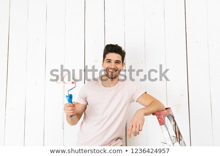 Stockfoto: Photo Of Brunette Man 20s Painting White Wall And Making Renovat
