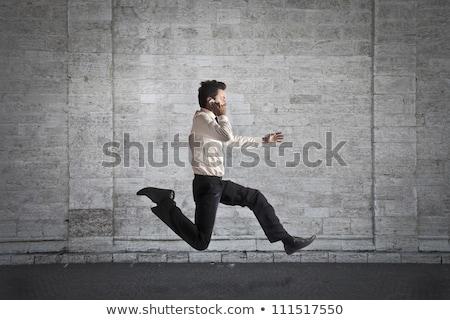 Scared businessman talking on mobile phone Stock photo © deandrobot