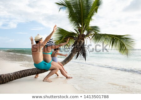 family sitting together on palm tree trunk at beach stock photo © andreypopov