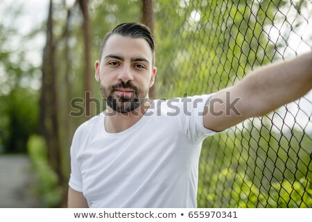 pretty men standing near chain link fence Stock photo © Lopolo