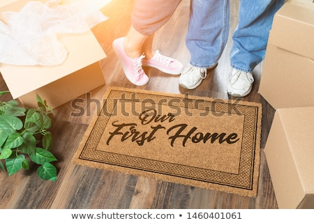 man and woman unpacking near new home welcome mat moving boxes and plant stock photo © feverpitch