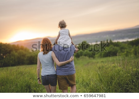 father with their cute little daughter on shoulder in meadow stock photo © lopolo