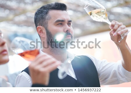 Young confident sommelier with glass of cabernet sauvignon Stock photo © pressmaster