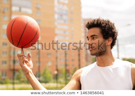 Young professional basketball player in white t-shirt holding ball on forefinger Stock photo © pressmaster