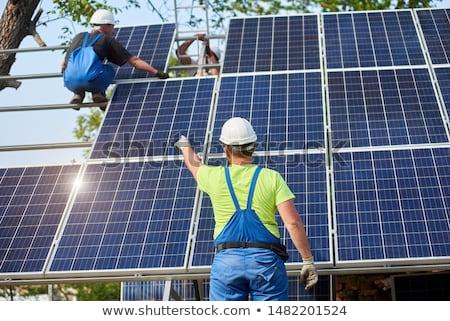 hands of professional technician or engineer installing solar panels stock photo © pressmaster