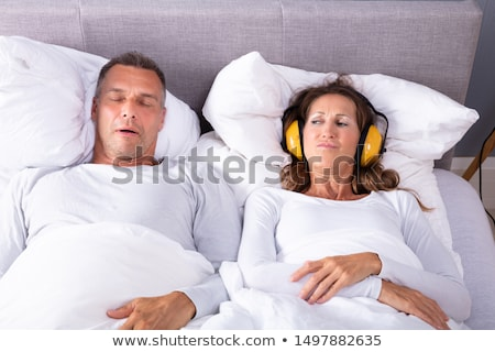 Woman Covering Her Ears With Headphones While Man Snoring Stock photo © AndreyPopov
