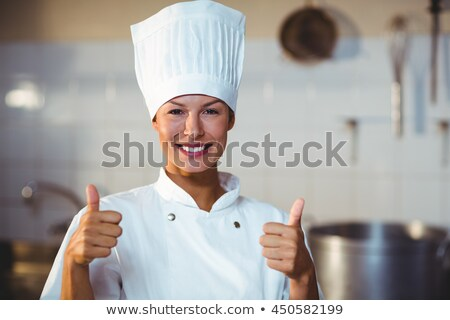 female chef showing thumbs up in kitchen at hotel stock photo © wavebreak_media
