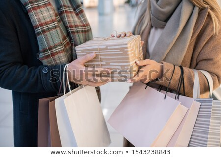 Midsection of young casual couple holding paperbags and wrapped giftbox Stock photo © pressmaster