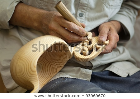 Master wood-carver made using a special knife wooden national dish - a ladle with a patterned handle Stock photo © galitskaya