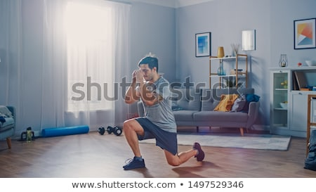 Young handsome man doing sport exercises at home  Stock photo © Elnur