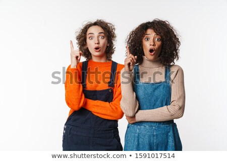 Portrait of shocked multinational women pointing fingers upward Stock photo © deandrobot
